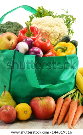 Green shopping bag with grocery products on white background - stock photo