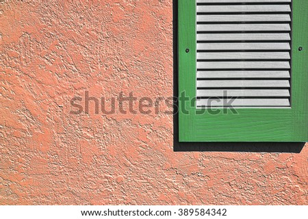 Green shutter on coral stucco exterior wall - stock photo
