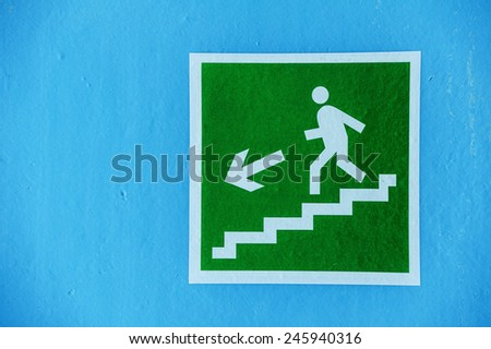 Green sign evacuation down the stairs on the blue wall. - stock photo