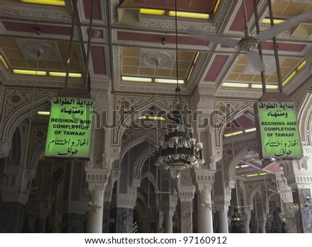 Green signage inside Masjidil Haram denotes the beginning and completion of tawaf (circumambulation). Muslim pilgrims circumambulate the Kaabah 7 rounds. - stock photo