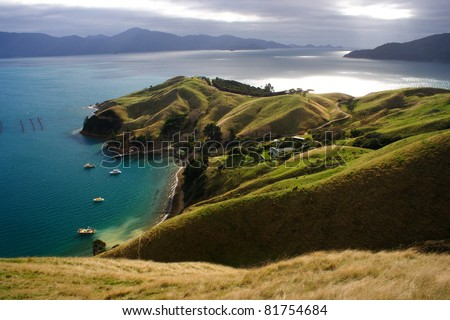 Green slopes and coastal farm on the Marlborough Sounds region of South island of New Zealand - stock photo