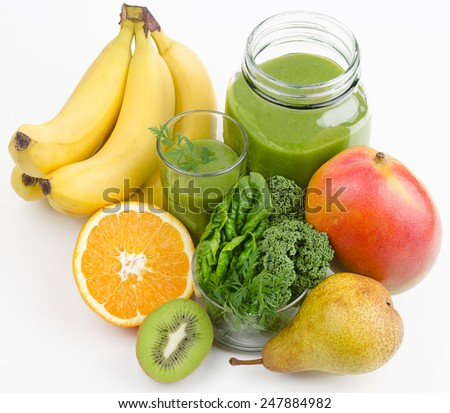 Green smoothie in a glass and in a open jar with fresh kale, spinach and carrot leafs. A raw, healthy and vegan drink made of green leafs and fruits. - stock photo