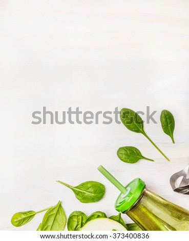 Green smoothie  in glass bottle with spinach leaves on white wooden background, top view, border. Superfoods and health or detox  diet food concept. - stock photo