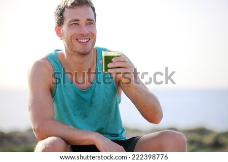 Green smoothie man drinking vegetable juice after running sport fitness training. Healthy eating lifestyle concept with young man outdoors. - stock photo