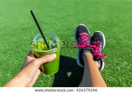 Green smoothie woman drinking plastic cup breakfast takeaway juice to go after morning run in summer park. Healthy lifestyle sporty person POV of hand holding drink with running shoes feet selfie. - stock photo