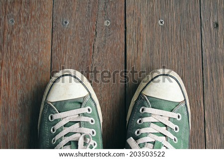 Green sneakers from an aerial view on wooden floors. Top view. - stock photo