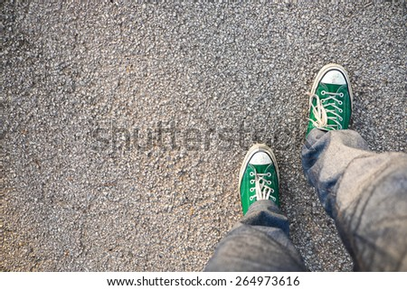 green Sneakers shoes walking on concrete top view , Canvas shoes walking on concrete - stock photo