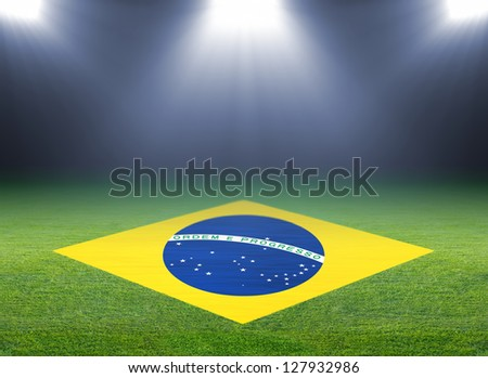 Green soccer field, brazil flag, bright spotlights, illuminated stadium - stock photo