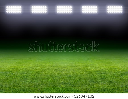 Green soccer field, row of bright spotlights, illuminated stadium in night - stock photo