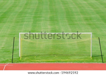 Green soccer field with gate and yellow net