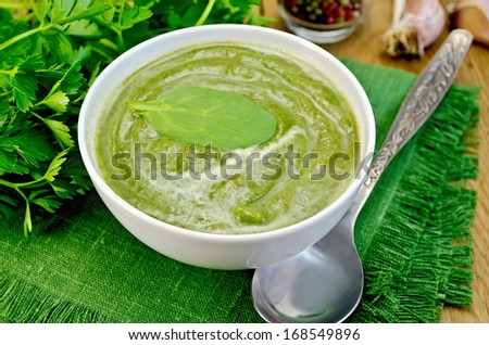 Green soup puree in a white bowl with spoon on a napkin, spinach, parsley, garlic on a wooden boards background - stock photo