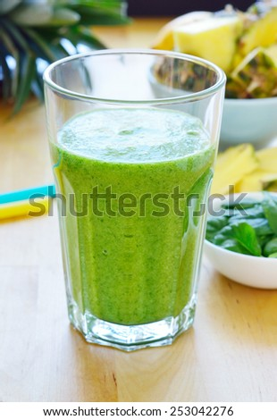 Green spinach and pineapple smoothie on table. Fruit smoothie made with baby spinach leaves, pineapple, banana and pear - stock photo