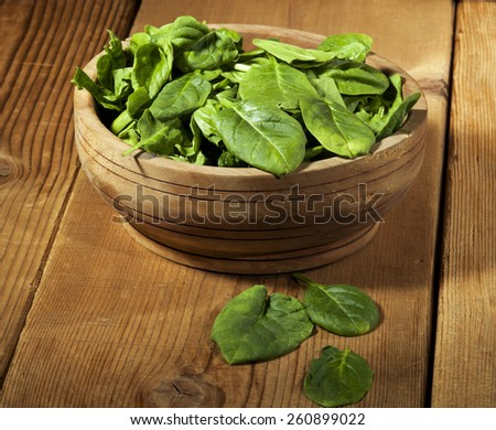 Green spinach in wooden bowl on a wooden background - stock photo