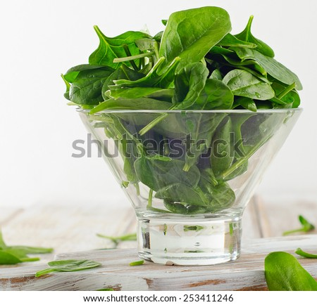 Green Spinach leaves in glass bowl. Selective focus