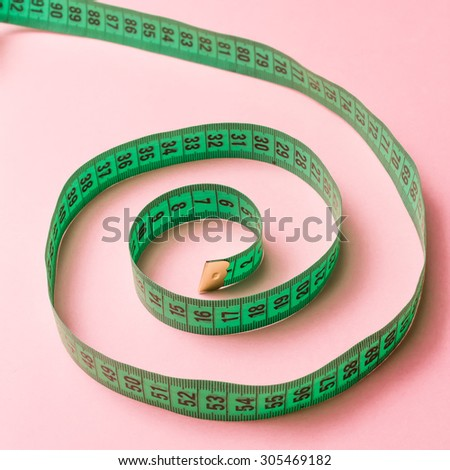 Green spiral tailor measuring tape on pink background  - stock photo