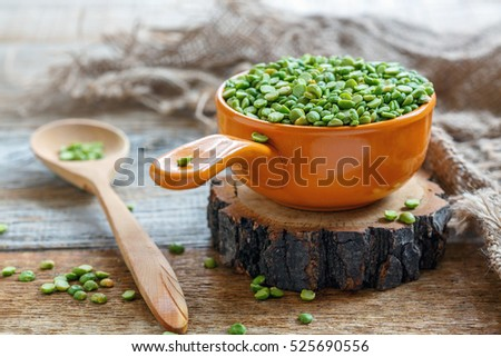 Green split peas in a ceramic bowl on old rustic background.