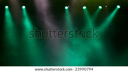 Green spotlights with smoky air as background - stock photo