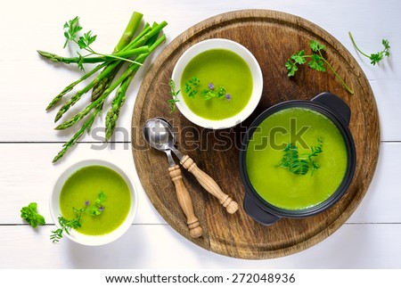 Green spring pureed asparagus soup served in plates decorated with various garden herbs - stock photo