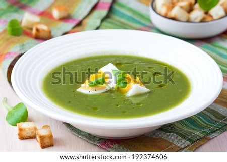 Green spring, summer healthy cream soup with herbs, egg, croutons, delicious homemade dinner - stock photo