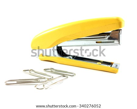 Green stapler and paper clip on white background