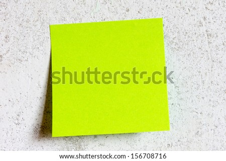 Green sticky note with shade on grey - stock photo