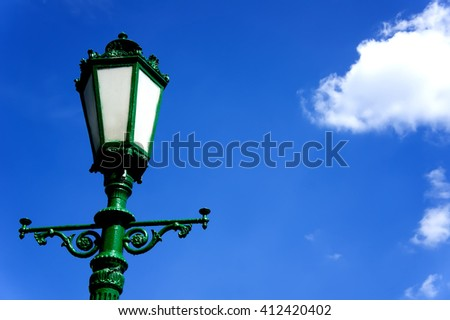 green street lamp post on blue sky background - stock photo