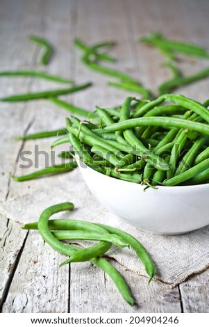 green string beans in a bowl on rustic wooden table - stock photo