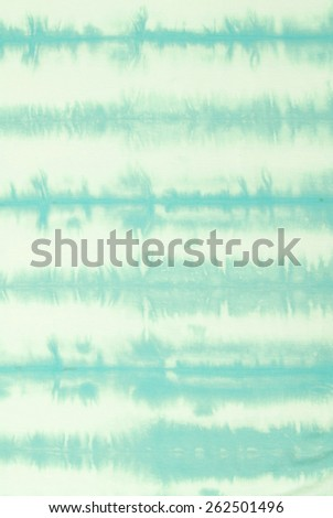 green strip tie dyed pattern on cotton fabric.  - stock photo