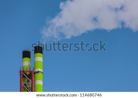 Green striped factory chimney with smoke - stock photo