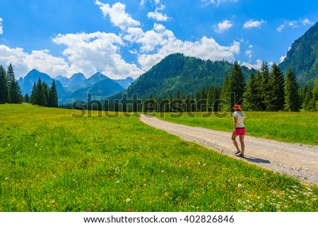 Green summer landscape and young woman tourist walking on hiking trail in High Tatra Mountains, Slovakia