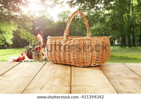 green sunny day in park and empty basket and yellow wooden table and woman in red dress