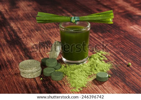 Green superfood chlorella, wheat grass, barley grass and spirulina pills, powder and ground on wooden background. Detox. - stock photo