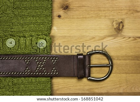 Green sweater and brown leather belt on rustic wood background with copy space. - stock photo