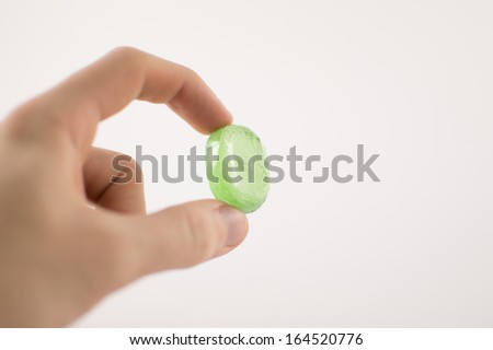 Green Sweet held in hand - stock photo