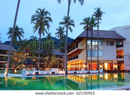 Green swimming pool near open-air restaurant in night illumination, Koh Chang island, Thailand - stock photo