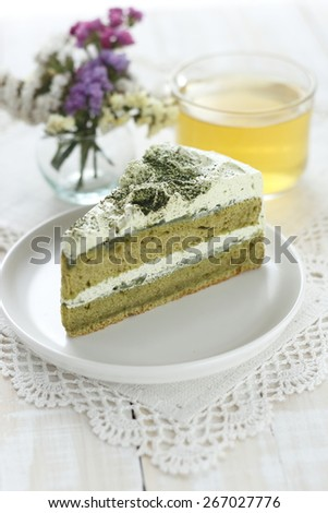 green tea cake with a a cup of hot tea on white wooden background  - stock photo