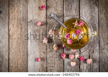 Green tea cup with teaspoon and dried rose buds on old wooden table, top view with copy space