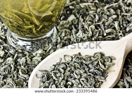 Green tea dry leafs on wooden spoon. - stock photo