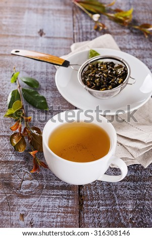 Green tea in a white ceramic cup over rustic wooden background - stock photo