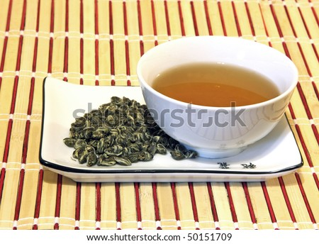 Green tea in a white cup and with tea leaves on a porcelain saucer - stock photo
