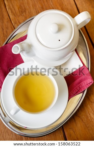 Green tea in cup with teapot