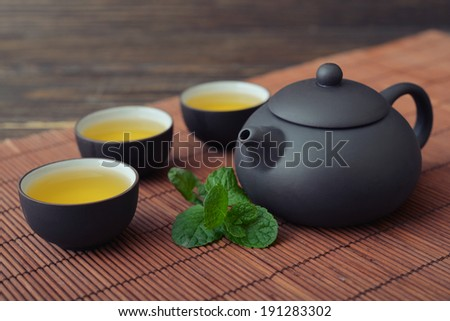 Green tea in cups with mint and teapot on bamboo mat - stock photo