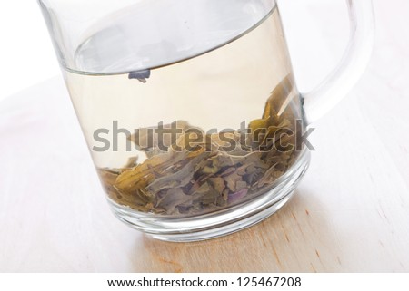 Green tea in glass cup with leafs, closeup on wooden table