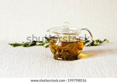 Green tea in glass teapot with fresh dry mint leaves on textured linen background. Focus on teapot - stock photo
