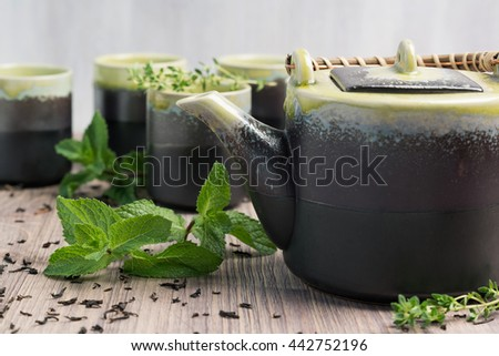 Green tea in teapot with small cups over, wooden background. Black ceramic teapot and cups on wooden table