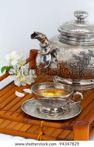 green tea in the cup, teapot, flowers, apple trees on a bamboo tray - stock photo