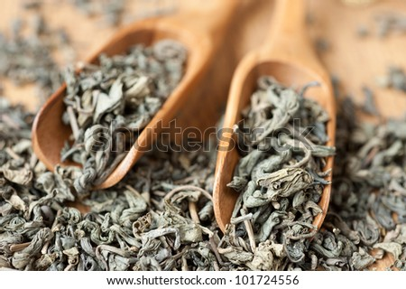 Green tea in wooden spoons - stock photo