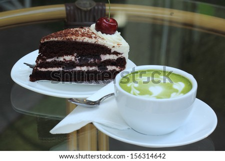 Green tea Latte and Black forest cake  - stock photo