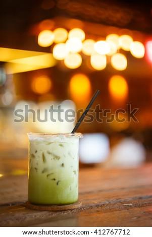 Green Tea Latte in Beaker with Cafe's Bokeh Background - stock photo