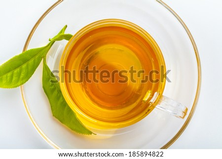 Green tea leaf and glass cup of black tea isolated on white background